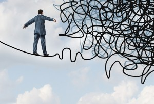 Risk confusion business concept with a businessman on a high wire tight rope walking towards a tangled mess as a metaphor and symbol of overcoming adversity in strategy and finding solutions through skilled leadership facing difficult obstacles.